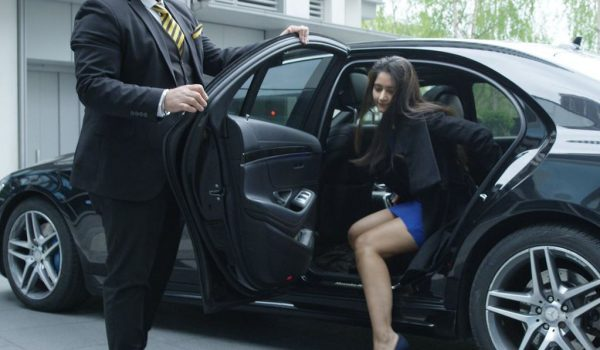 blue dress woman getting out of chauffeured car